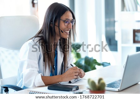 Shot of female doctor talking with colleagues through a video call with a laptop in the consultation.