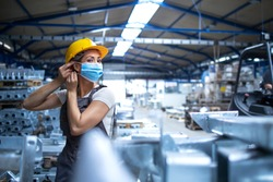 Shot of female factory worker in uniform and hardhat putting on face mask in industrial production plant. People working during COVID-19 pandemic.
