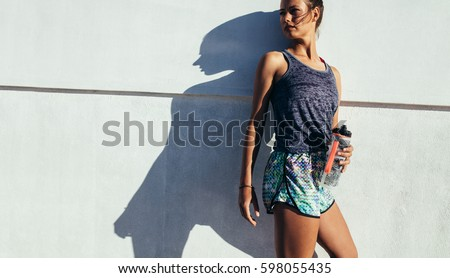 Shot of fit runner standing against a wall outdoors. Sporty woman relaxing after running exercise. #598055435