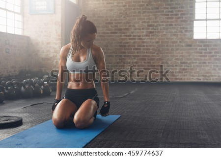 Shot of fitness woman sitting on exercise mat and looking at her triceps. Muscular woman working out at the fitness club.