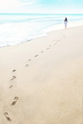 Shot of footprints with woman walks on the tropical beach. Shot in maldives