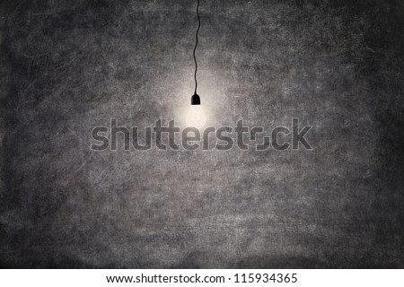 Shot of glowing light bulb in front of empty blackboard (copy space)