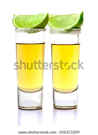 Shot of Gold Tequila with Slice Lime on white background
