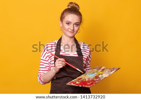 Shot of good looking student with pleasant look, wears striped shirt and brown apron, looks at camera, holds brush and palette of colors, poses against yellow background. Creation and art concept. #1413732920