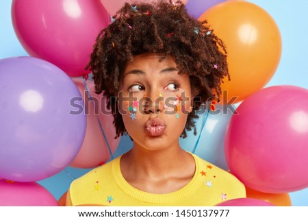 Shot of good looking woman pouts lips at camera, wants to kiss guests coming on party, has curly Afro hair, decorative colorful little stars on head face and clothes looks away, balloons in background