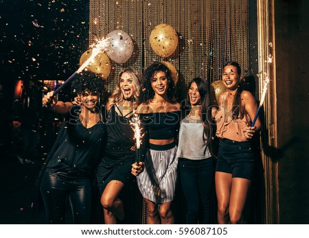 Shot of group of young women celebrating new years eve at the pub. Group of female friends with sparklers partying in nightclub. #596087105