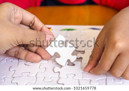 Shot of hand holding puzzle. Symbol for connection, teamwork, together, success, strategy #1021659778