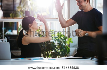 Shot of happy and successful business colleagues giving high five in office.