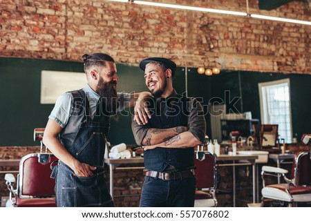 Shot of happy barber with client standing at barbershop and smiling. Two man at salon, hairstylist and customer.