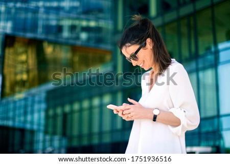 Shot of happy businesswoman text messaging while standing on the street. stock photo