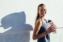 Shot of happy female runner standing outdoors holding water bottle and smiling. Fitness woman taking a break after workout.