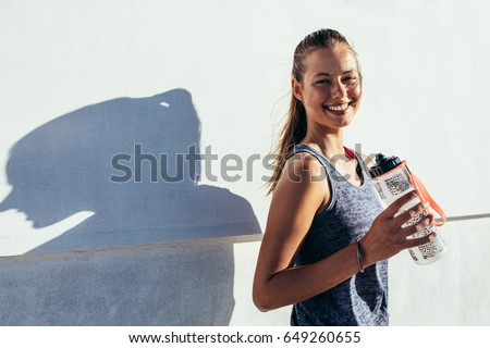 Shot of happy female runner standing outdoors holding water bottle and smiling. Fitness woman taking a break after workout. #649260655