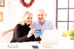 Shot of happy senior couple shopping online. Attractive elderly woman holding bank card in her hand while senior man sitting behind their laptop and making online payment.