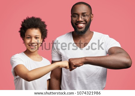 Shot of happy smiling father and son with pleasant smile greet happily and congratulate with successful winning of competition, give fist bump to each other, demonstrate friendly relationship