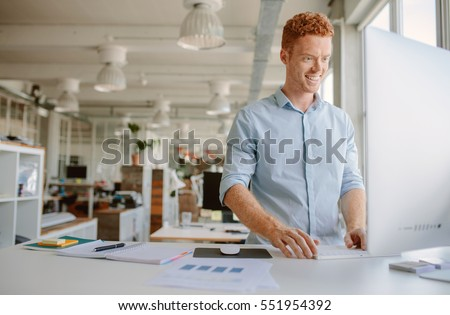 Shot of happy young man standing at his desk and working on computer. Businessman working in modern office.