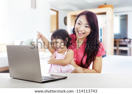 Shot of happy young mother and daughter with ultrabook laptop computer. shot at home