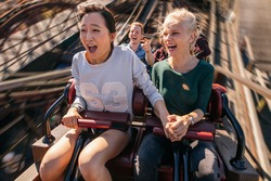 Shot of happy young people riding a roller coaster. Young women and men having fun on amusement park ride.
