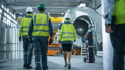 Shot of Heavy Industry Engineers and Workers Walking through Pipe Manufacturing Factory. Modern Facility for Design and Construction of Oil, Gas and Fuels Transport Pipeline.