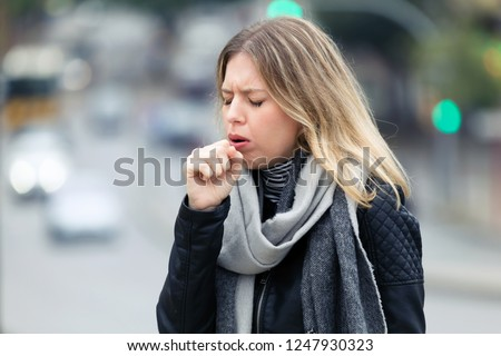 Shot of illness young woman coughing in the street. Stock photo ©