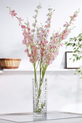 Shot of interior design. In the middle there is a floral composition with whitey-pink orchid twigs in a waterglass. On the blurred background there is a wall shelf with photo frame and woven basket.