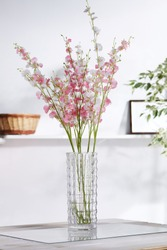 Shot of interior design. There is a floral composition in the middle with whitey-pink orchid twigs in a waterglass. On the blurred background there is a wall shelf with photo frame and woven basket.