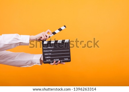Shot of isolated hands on yellow background holding a clapper. Teenage girl holding clapper in studio.