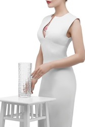 Shot of lady's lower face's part with floral tattoo on her chest, posing in a dress on white background. The woman with red lipstick is touching a cylindrical waterglass, which stands on high chair.