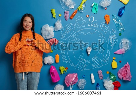 Shot of lovely woman has two pigtails, makes heart gesture over chest, dressed in orange sweater and jeans, demonstrates love to nature and environment cares about ecology, cleaning. Plastic pollution