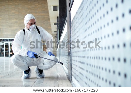 Shot of male person in white chemical protection suit doing disinfection of public areas to stop spreading highly contagious corona virus. Stop coronavirus or COVID-19.