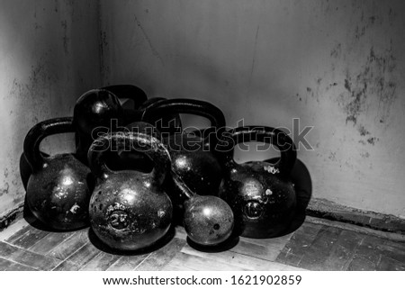 Shot of many kettlebells of different weights and dumbbells laying on parquet floor indoors. Personal equipments for strength training, bodybuilding and health strengthening. Healthy lifestyle concept
