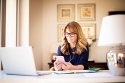 Shot of middle aged businesswoman using earphone while sitting behind her laptop and text messaging on  mobile phone. Businesswoman working from home. Home office.