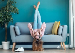 Shot of motivated young woman listening to music with smartphone while lying down on sofa at home.