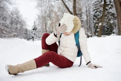 Shot of person during falling in snowy winter park. Woman slip on the icy path, fell and lies. Danger of season trauma.