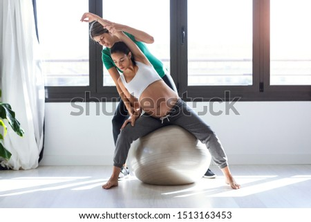 Shot of physiotherapist helping to beautiful pregnant woman for doing pilates exercises with ball preparing for childbirth.