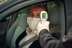 Shot of policeman measuring a healthy senior adult's body temperature with infrared thermometer in his car