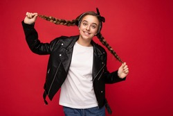 Shot of pretty positive smiling brunette little female teenager with pigtails wearing stylish black leather jacket and white t-shirt for mockup standing isolated over red background wall looking at
