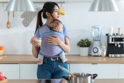 Shot of pretty young mother with little baby in sling drinking coffee in the kitchen at home.