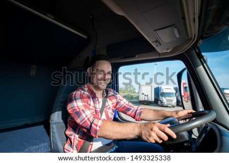 Shot of professional truck driver in casual clothing wearing seat belt on and driving his truck to destination. Smiling trucker enjoying his job. Transportation services.