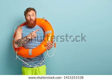 Shot of puzzled surprised redhaired male rescuer with lifebuoy, shows direction, points at upper right corner, tells impressive story about saving sinking person. Man on awesome summer vacation