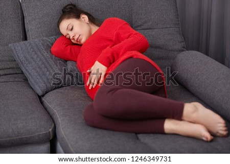 Shot of restful pregnant woman keeps hand on tummy, wears casual clothes, lies on comfortable sofa, going to take nap, rests at home alone. Thoughtful expectant mother feels lonely and relaxed #1246349731