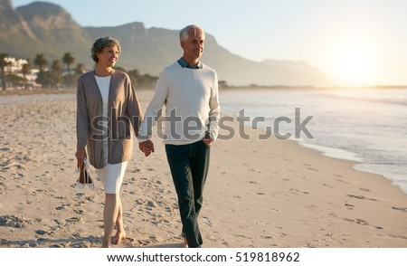Shot of senior couple walking along beach together holding hands.