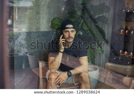 Shot of serious bearded male freelancer,  wears casual t shirt, sporty casual style, speaks with partner or colleague via cell phone, waits for coffee with dessert, has concentrated strict expression. #1289038624