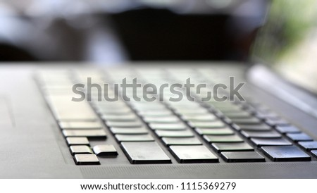 Shot of silver colored laptop keyboard with computer screen partially visible. Macro lens used