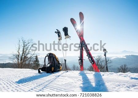 Shot of skiing equipment - skis, backpack, sticks, gloves and action camera on monopod, on top of the ski slope at ski resort in the mountains winter sports lifestyle extreme active concept #721038826