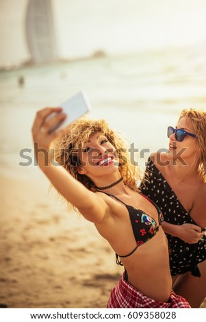 Shot of smiling young women taking pictures with mobile phone on the beach.
