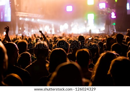 Shot of some cheering fans during a life concert, visible noise due high ISO, soft focus, shallow DOF, slight motion blur