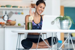 Shot of sporty beautiful woman having an online video call via laptop computer while drinking detox juice in the kitchen at home.