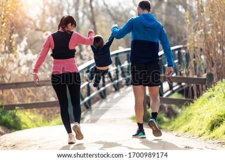 Shot of sporty young couple with her little son playing and enjoying the time together outdoor. stock photo