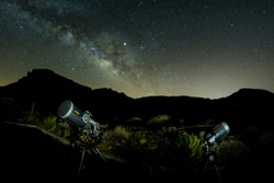 Shot of stars and milky way at hight sky via fish eye lens. Two telescopes ready for observation in the foreground. No Moon. Long Exposure. National Park Teide, Tenerife.