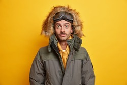 Shot of surprised young man with snowboard goggles stares bugged eyes stunned by stormy blizzard dressed in winter outerwear isolated over yellow background. Shocked male skier has active rest